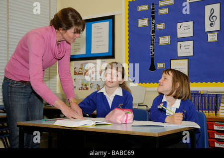 Schoolgirls in a classroom Students working together with their female teacher - Stock Photo
