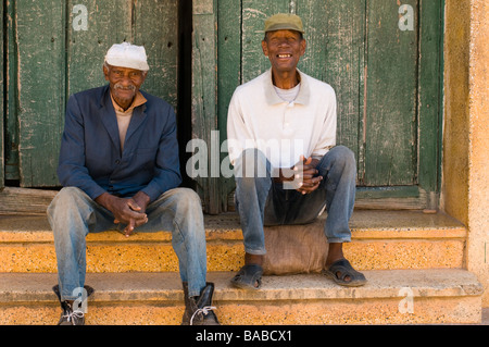 Two elderly men in caps sitting on the front steps of their home in Trinidad, Cuba. - Stock Photo