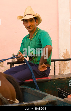 Young Cuban cowboy in straw hat on a wagon in the town of Trinidad, Cuba. - Stock Photo