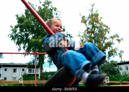 Smiling boy on a swing Linkoping Sweden - Stock Photo