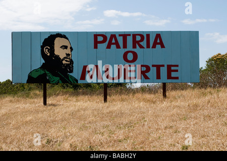 Rural billboard in Cuba with a revolutionary slogan and drawing of Fidel Castro - Stock Photo