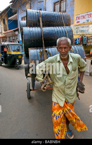 Street trader transporting  drums of coconut oil from one depot to stall in Old  Kochin's spice area, Kerala India - Stock Photo