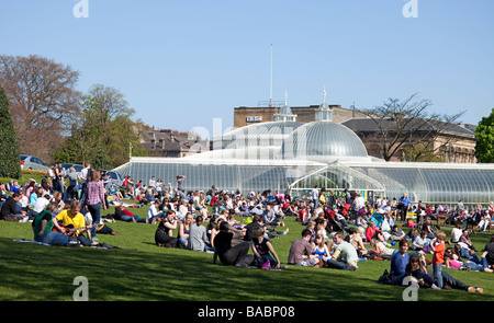 Small groups of people on a lawn in front of the Kibble Palace in Glasgow's Botanic Gardens, enjoying a sunny April - Stock Photo