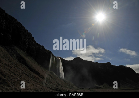 A view into the sun of the 60m high Seljalandsfoss Waterfall, Eyjafjoll, Southern Iceland - Stock Photo