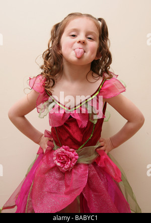Child poking out tongue with her hands on her hips - Stock Photo