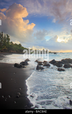 Dramatic sunrise over Hana Bay on the northeast coast of Maui, Hawaii, in the town of Hana - Stock Photo