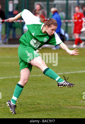 Young female footballer in action - Stock Photo