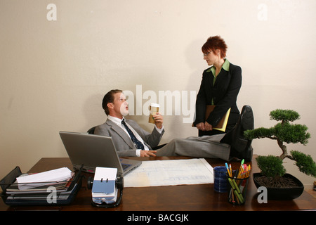 Businessman sitting in an office with his secretary standing beside him - Stock Photo