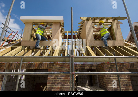 Carpenters working on the roof of a new house. - Stock Photo