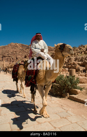 A Jordanian man wearing a typical red and white checked keffiyeh riding a camel in the ancient Nabatean city of - Stock Photo