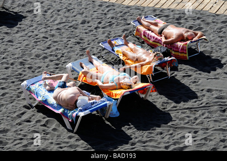 Men and women sunbathing on a black sand beach Tenerife Canary Islands - Stock Photo