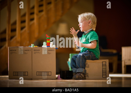 Toddler saying Mom using sign language while playing with toys on cardboard boxes - Stock Photo