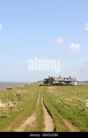 Coastal erosion near Waxham,North Norfolk,England,UK. Abandoned houses on the cliff edge with gardens falling into - Stock Photo