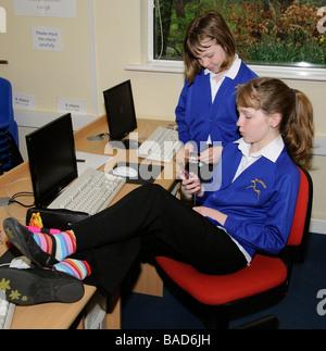 Schoolgirls using mobile telephones in a classroom - Stock Photo