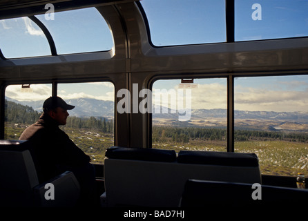 Train passenger looking out train car window at western  landscape of United States - Stock Photo