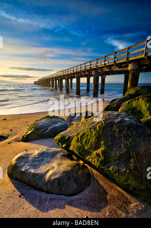 A large wooden pier at sunset with rocks covered in green moss all lit with beautiful golden light - Stock Photo
