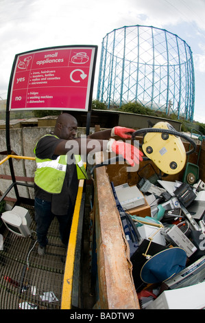Factory Lane Recycling and Reuse Centre in Croydon UK Council worker Isaac Fletcher at the small appliances container - Stock Photo