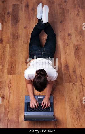 Young woman in casual clothing lying on a wooden floor using a laptop computer - Stock Photo