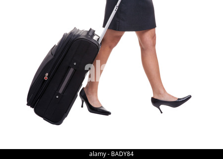 A businesswomans legs in short skirt pulling a suitcase isolated on white background - Stock Photo