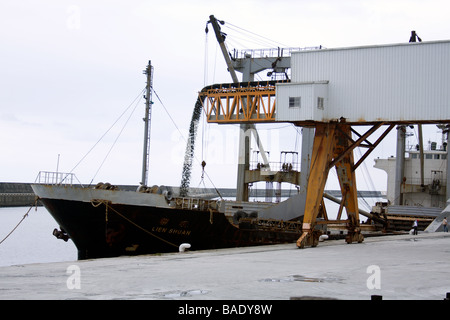 'Lien Shuan' general cargo ship being loaded with gravel from conveyor belt at bulk cargo terminal area, warehouse - Stock Photo