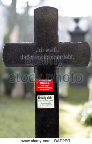 Black stone grave cross with warning stickers on it, risk of accident and right to use has expired - Stock Photo