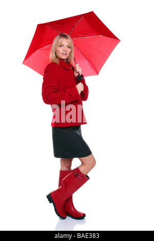Beautiful young woman wearing a red coat and wellie boots holding a red umbrella isolated on white background - Stock Photo
