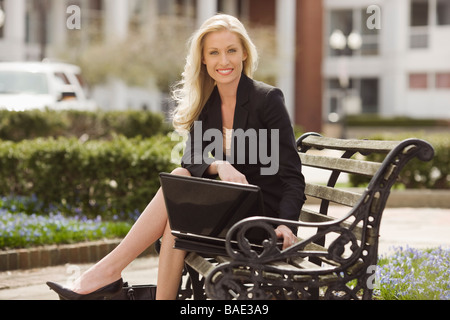 Business Woman Using Laptop on Park Bench