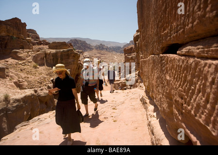 Tourist hike up the steep track on Jabal Al-Deir on their way to visit the Monastery in the ancient city of Petra, - Stock Photo