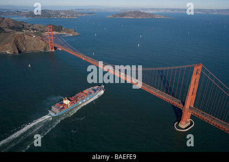 aerial view above loaded MOL container ship passing under the Golden Gate bridge into San Francisco Bay - Stock Photo