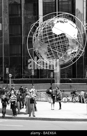 Pedestrians in NYC stand near a globe sculpture while waiting to cross the street. (Also available in color.) - Stock Photo