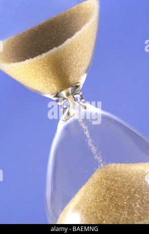 Hourglass counting the time is running out - Stock Photo