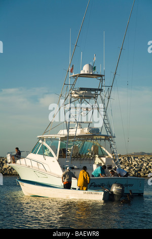 MEXICO La Playita Men selling bait fish from motorboat next to larger fishing boat in harbor - Stock Photo