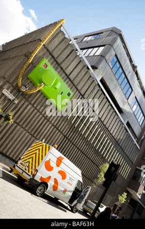 Electricity repair van outside a building in central London. The build appears to have a giant plug and socket on - Stock Photo