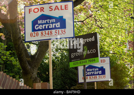Row of 'for Sale ' and 'To Let' signs in a leafy North London suburb. - Stock Photo