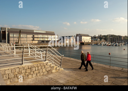A couple walking at Victoria Dock and the Galeri arts centre Caernarfon Gwynedd north wales summer evening - Stock Photo