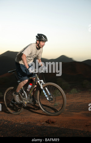 A Mountain biker riding his MTB in the mountains. - Stock Photo