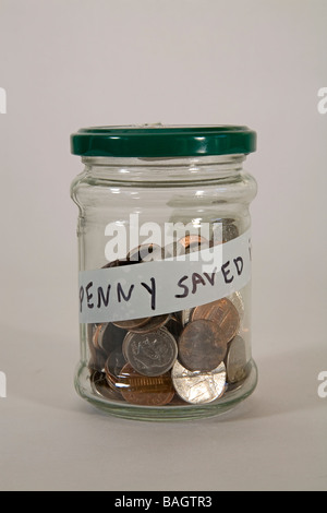 A jar filled with coins, a penny saved is a penny earned. - Stock Photo