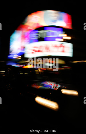London taxi driving through Piccadilly Circus, London, UK - Stock Photo