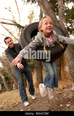 Father pushing daughter on tire swing - Stock Photo