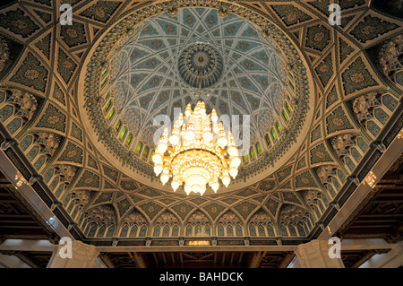 Muscat Oman Grand Mosque interior the Prayer Hall with large chandelier hanging below the ornate dome - Stock Photo