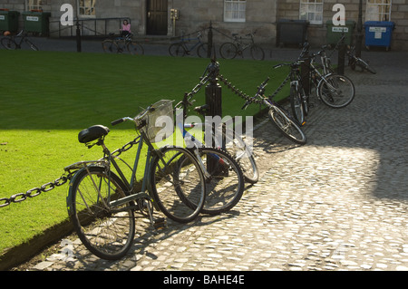 Traditional bicycles locked against chain fence at Trinity College, Dublin, Ireland - Stock Photo