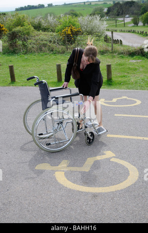 Wheelchair parking place and sign woman preparing chair for use - Stock Photo