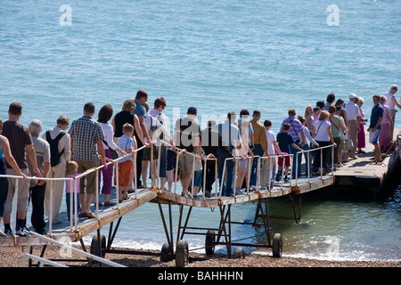 [People queuing] for boat trip from beach Eastbourne - Stock Photo