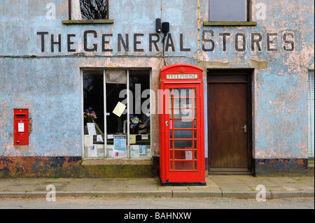 A red telephone box outside a derelict General Stores in Mathri Pembroke Wales - Stock Photo