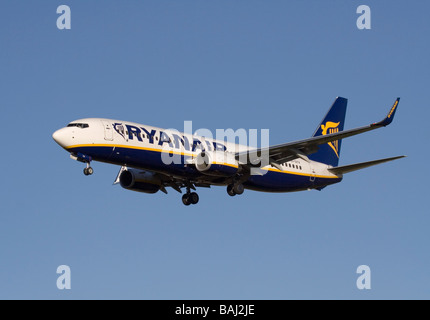 Cheap air travel and mass tourism. Ryanair Boeing 737-800 jet airplane on final approach against a clear blue sky - Stock Photo