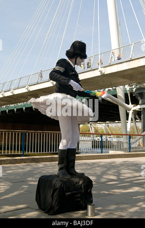 Street performer, dressed as a policeman in ballet dress, entertaining tourists, on Southbank in London - Stock Photo