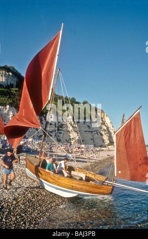 Launching a Beer lugger sailing boat at Beer beach Devon England UK Europe - Stock Photo