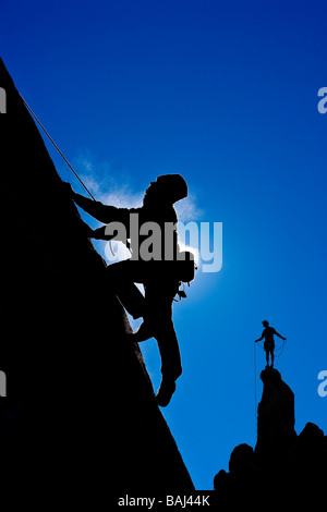 A climber is silhouetted as he makes his way up a steep rock face in the Sierra Nevada Mountains California - Stock Photo