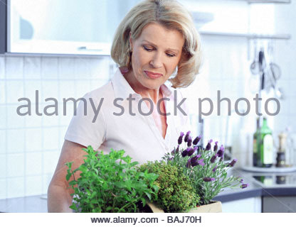 middle aged woman holding basket with herbs in her hands - Stock Photo