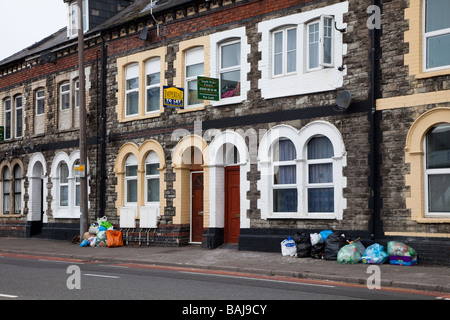 Rubbish in street outside row of terraced houses with to let signs Cardiff Wales UK - Stock Photo